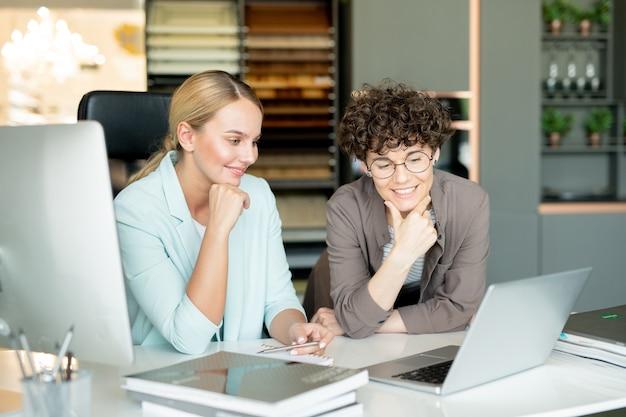 Twee vrouwelijke ondernemers kijken aandachtig naar laptopvertoning tijdens het kijken naar online cursus voor ontwerpers