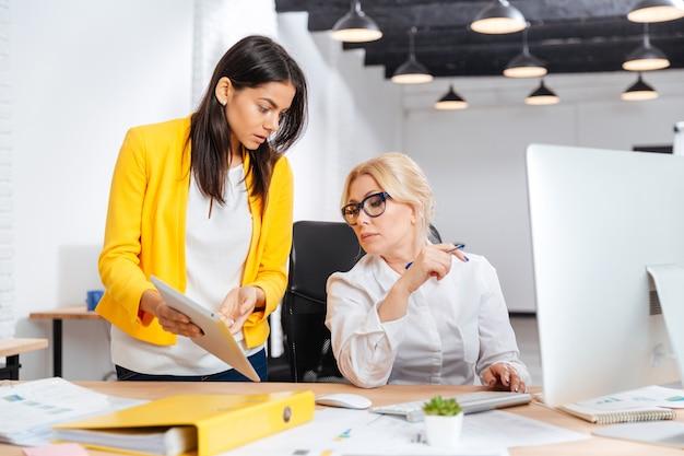 Twee vrouwelijke ondernemers werken samen in kantoor
