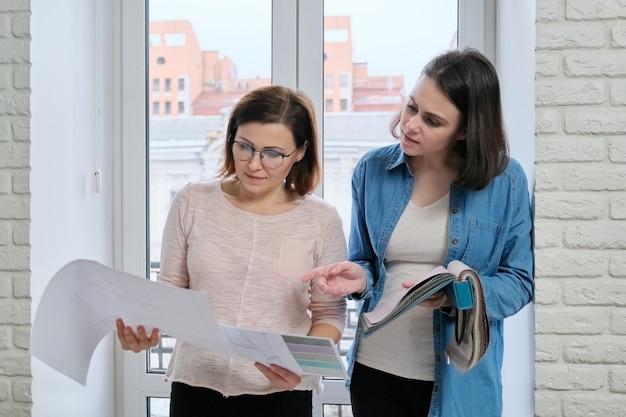 Twee vrouwelijke ontwerper en klant die stoffen kiezen voor gordijnen, meubelstoffering