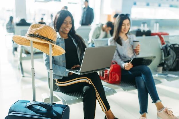 Twee vrouwelijke reizigers met laptops die op vertrek in luchthaven wachten.
