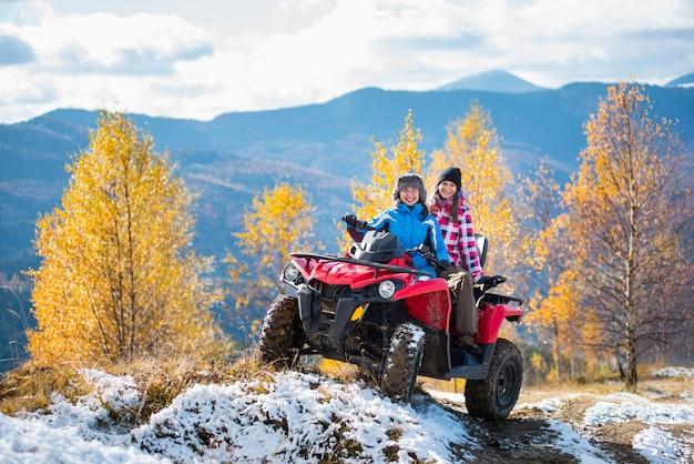 Twee vrouwelijke ruiters atv in jasjes en hoeden op een snow-covered sleep bij zonnige de herfstdag tegen bomen met gele bladeren en bergen