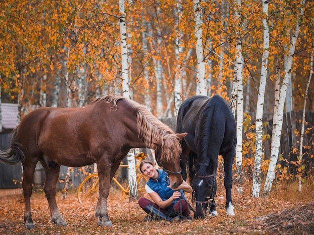 Twee vrouwelijke ruiters zitten naast de paarden op het gras