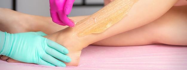 Twee vrouwelijke schoonheidsspecialisten waxen dames benen met hete suikerpasta in een beauty spa salon