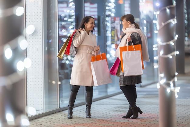 Twee vrouwelijke shopaholic-vrienden ontmoeten elkaar tijdens kerstinkopen buiten het winkelcentrum op een koude winterdag.