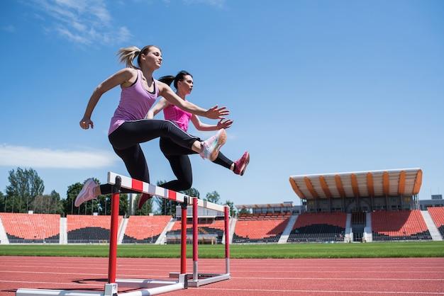 Twee vrouwelijke sportvrouwen springen over een obstakel. lopen met hindernissen. actieve levensstijl