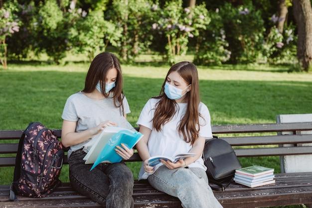 Twee vrouwelijke studenten die beschermende medische maskers dragen, bereiden zich voor op examens op een campusbankje. onderwijs op afstand. zachte selectieve focus.