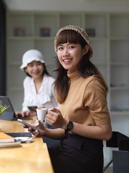 Twee vrouwelijke studenten nemen een koffiesnavel terwijl ze hun huiswerk maken met digitale tablets in café