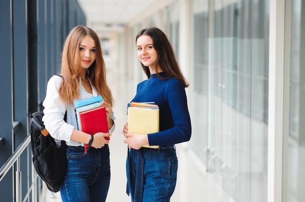 Twee vrouwelijke studenten staan met boeken in de gang van het college