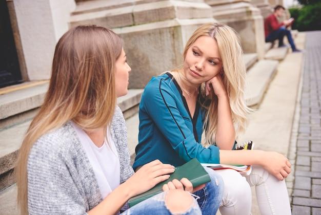 Twee vrouwelijke studenten zitten en praten