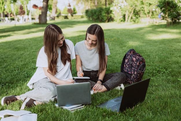 Twee vrouwelijke studenten zitten in het park op het gras met boeken en laptops, studeren en bereiden zich voor op examens. onderwijs op afstand. zachte selectieve focus.