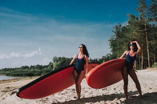 Twee vrouwelijke surfers die zich op strand in zwempakken bevinden.