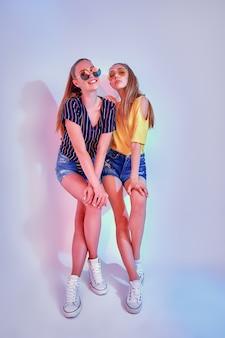 Twee vrouwelijke tieners in zonnebrillen en zomerkleding poseren in studio op witte achtergrond