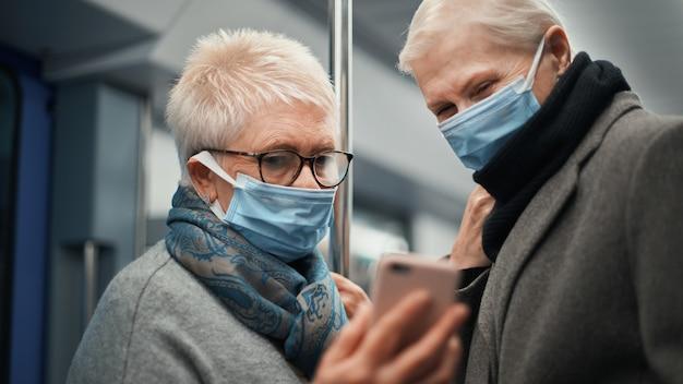 Twee vrouwelijke toeristen communiceren via videoverbinding tijdens een metrorit