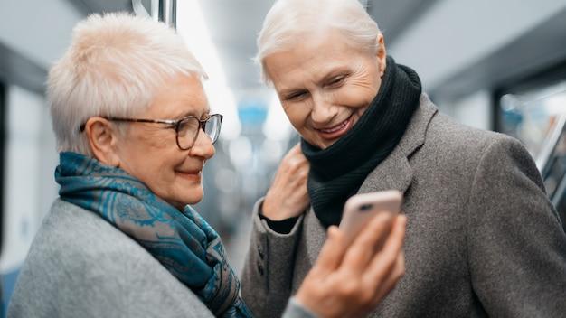 Twee vrouwelijke toeristen die een smartphone gebruiken tijdens een metrorit