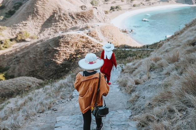 Twee vrouwelijke toeristen die zomerhoeden dragen, gaan de savanne-heuvel af