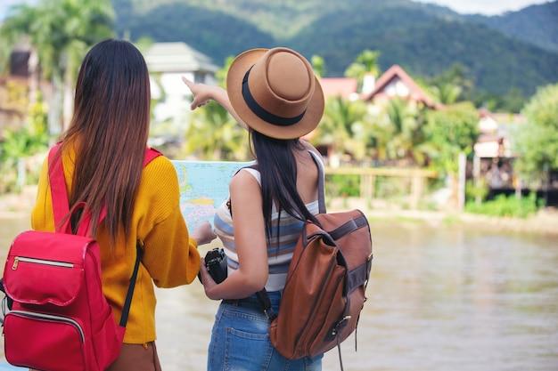 Twee vrouwelijke toeristen houden een kaart om plaatsen te vinden.