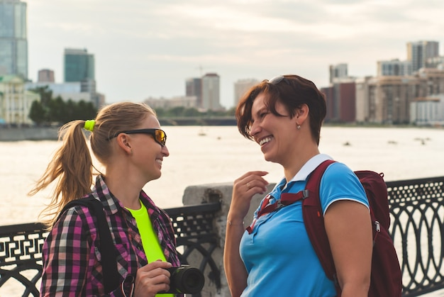 Twee vrouwelijke toeristen praten en lachen op de promenade tegen de rivier en het stadscentrum
