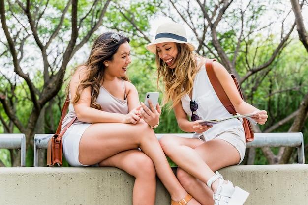 Twee vrouwelijke toeristenzitting in het park die mobiele telefoon bekijken