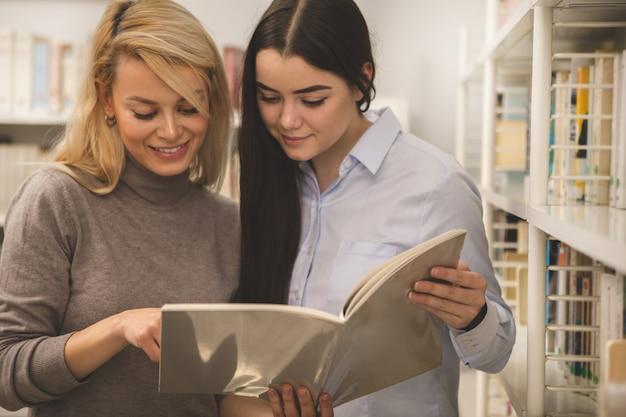 Twee vrouwelijke universiteitsvrienden die een boek bestuderen bij de bibliotheek
