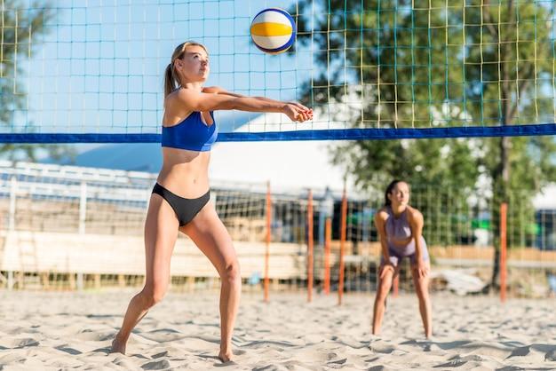 Twee vrouwelijke volleyballers die op het strand spelen