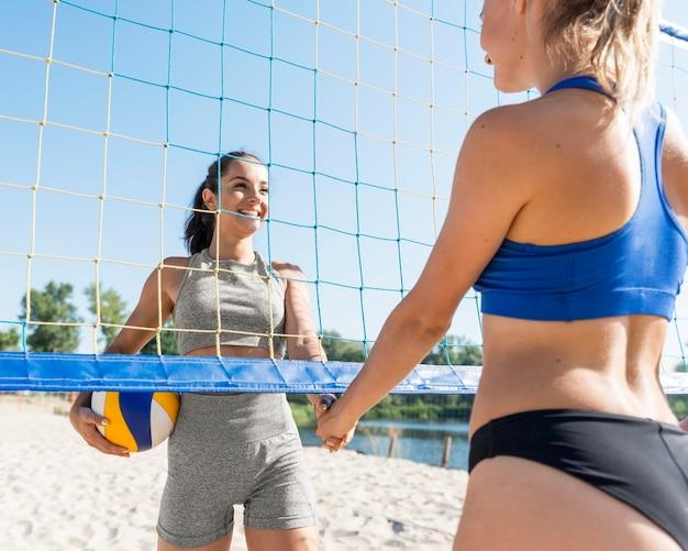 Twee vrouwelijke volleyballers met bal en net op strand