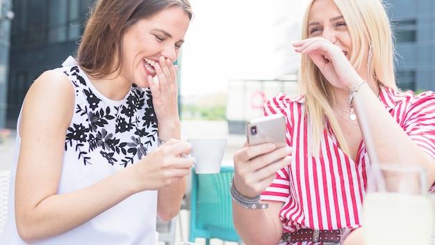 Twee vrouwelijke vrienden die bij openluchtcaf� genieten van
