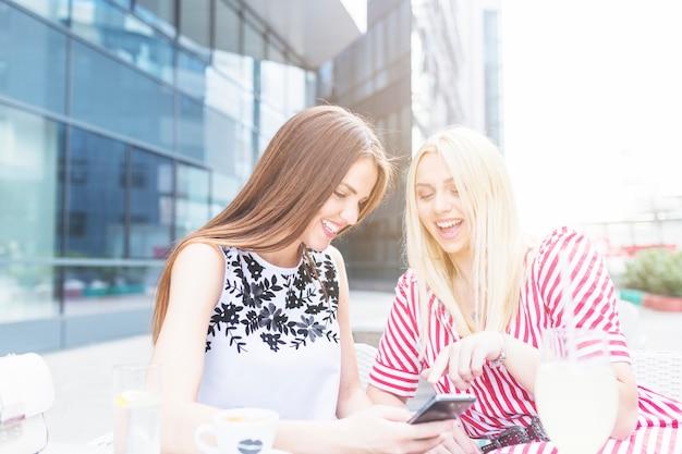 Twee vrouwelijke vrienden die bij openluchtkoffie zitten die mobiele telefoon met behulp van