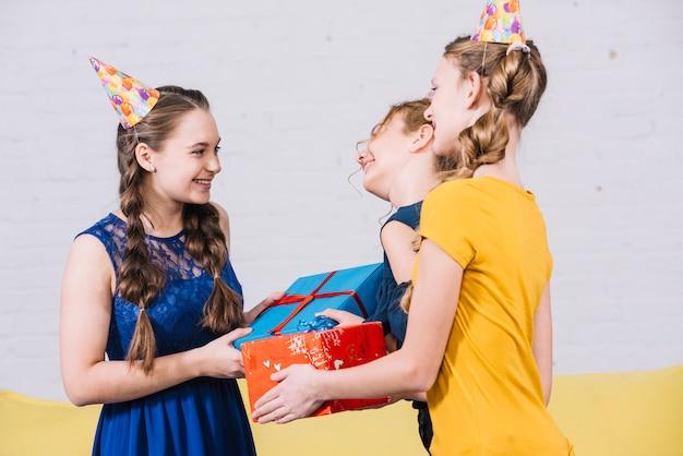 Twee vrouwelijke vrienden die de verjaardagsgeschenk geven aan het lachende meisje