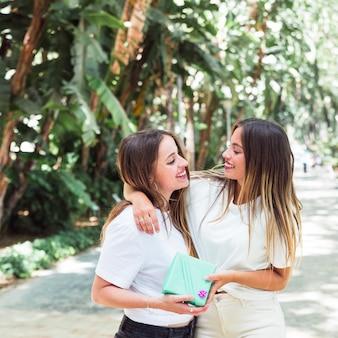 Twee vrouwelijke vrienden die elkaar bekijken die giftdoos houden