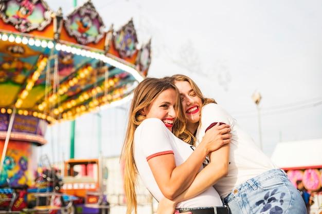 Twee vrouwelijke vrienden die elkaar omhelzen die zich voor carrousel bevinden