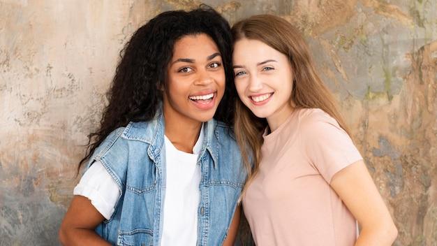 Twee vrouwelijke vrienden die en samen glimlachen stellen