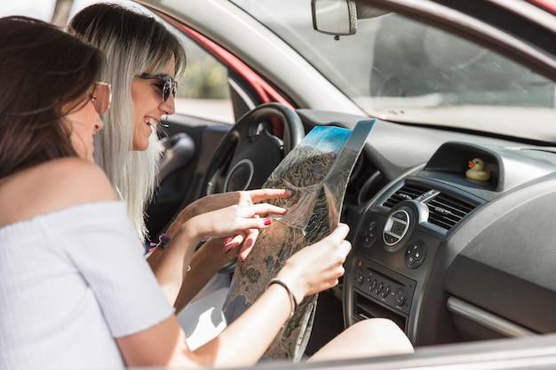 Twee vrouwelijke vrienden die in auto zitten die richtingen op kaart zoeken