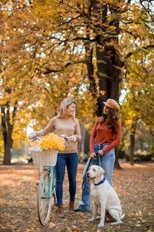 Twee vrouwelijke vrienden die in het gele de herfstpark lopen met hond en fiets