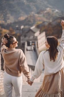 Twee vrouwelijke vrienden die langs de grote muur van china dichtbij het gevolg van peking lopen