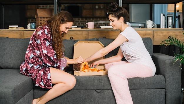 Twee vrouwelijke vrienden die pizzaplakken van doos nemen