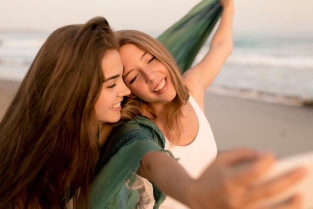 Twee vrouwelijke vrienden die selfie bij strand nemen