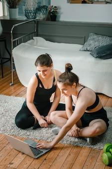 Twee vrouwelijke vrienden die thuis chatten, glimlachen en sporten