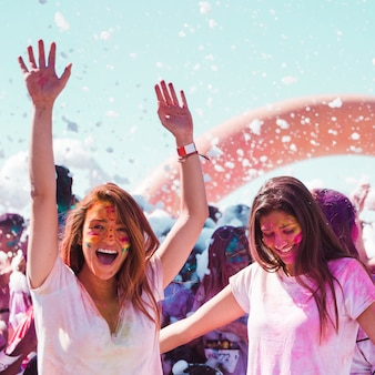 Twee vrouwelijke vrienden die van het holifestival genieten