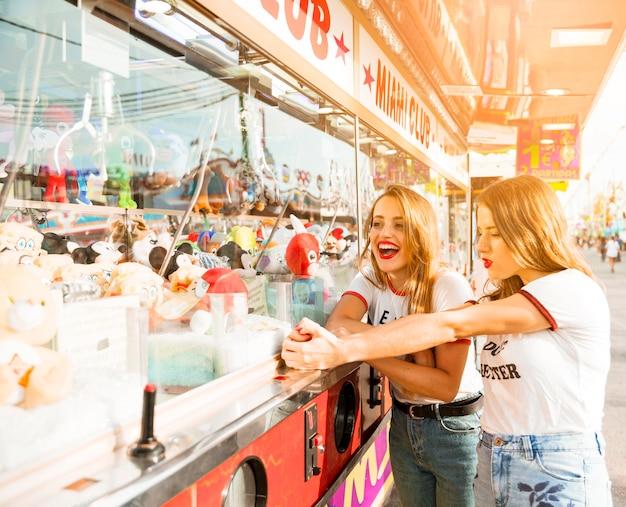 Twee vrouwelijke vrienden die zich dichtbij stuk speelgoed winkel bij pretpark bevinden