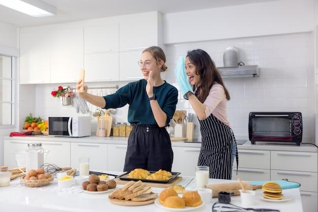 Twee vrouwelijke vrienden hebben plezier terwijl ze een selfie-ontbijt nemen in de keuken.