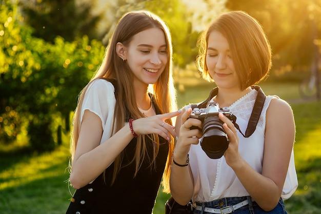 Twee vrouwelijke vrienden in het park fotograferen op een professionele camera. fotoshoot fotosessie in de stad.