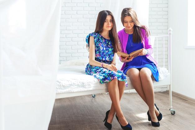 Twee vrouwelijke vrienden kijken boek thuis op bed.