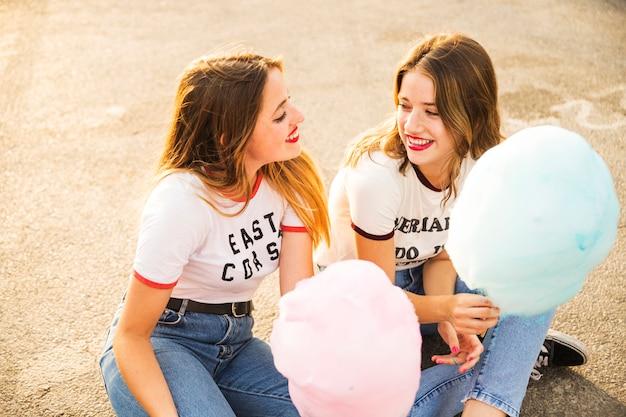 Twee vrouwelijke vrienden met suikerspin die elkaar bekijken