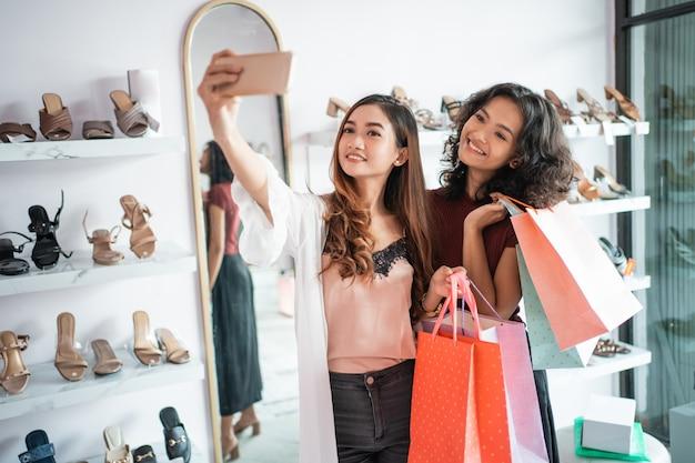 Twee vrouwelijke vrienden nemen een selfie tijdens het winkelen