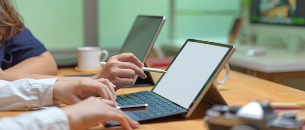 Twee vrouwelijke werknemers bespreken op hun project tijdens het werken met tablet