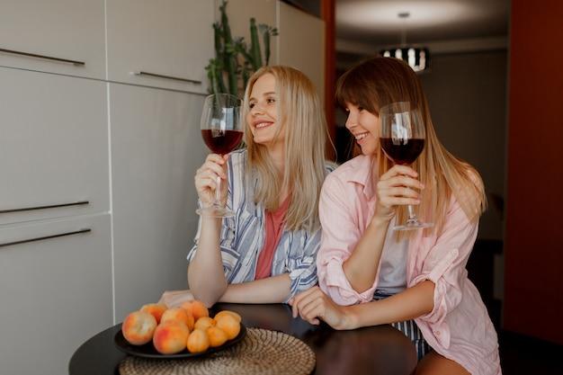 Twee vrouwen beste vrienden die wijn op keuken opjagen. gezellige huiselijke sfeer. bord met vers fruit.