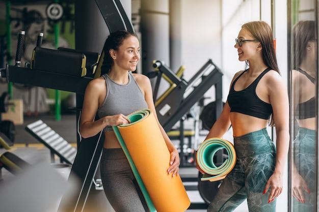 Twee vrouwen bij de gymnastiek die yogamat houden
