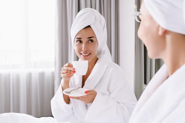 Twee vrouwen blijven in bed van appartement, hotel, ontbijten 's ochtends koffie, thee samen, dragen hoofddoeken en badjassen, vrije tijd, vakantie, luxe levensstijlconcept