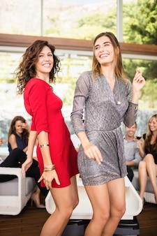 Twee vrouwen dansen en een groep vrienden kijken naar hun dans op feestje