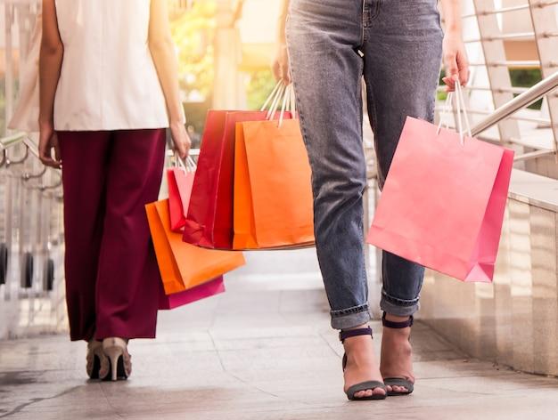 Twee vrouwen die aan het winkelen, verkoop, consumentisme en mensenconcept lopen.